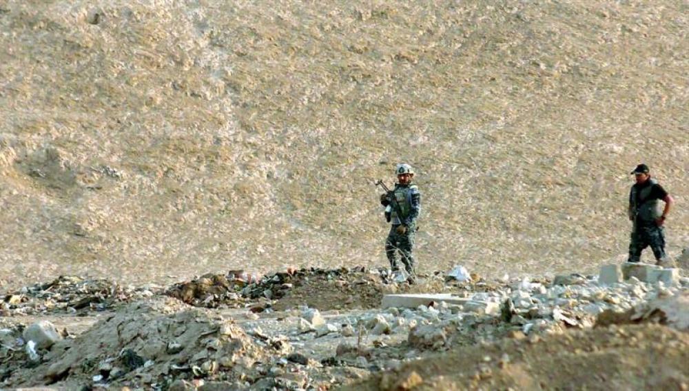 Oficiales iraquíes inspeccionan una zona en la que fue descubierta una fosa común, al sur de Mosul