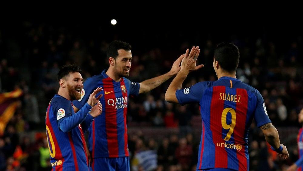 Messi, Busquets y Luis Suárez celebran un gol ante el Sporting