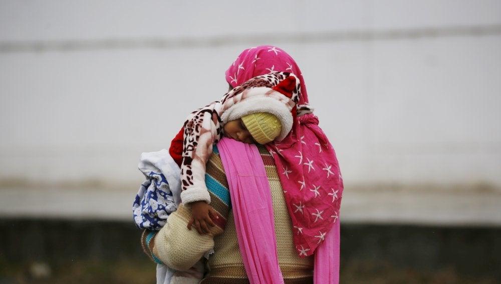 Una mujer lleva en brazos a su hijo bajo la lluvia en  Srinagar (India)