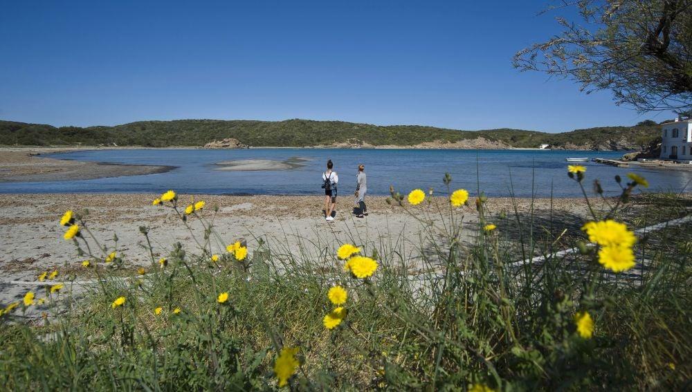 Dos personas caminan por la playa del Parque Natural de Es Grau