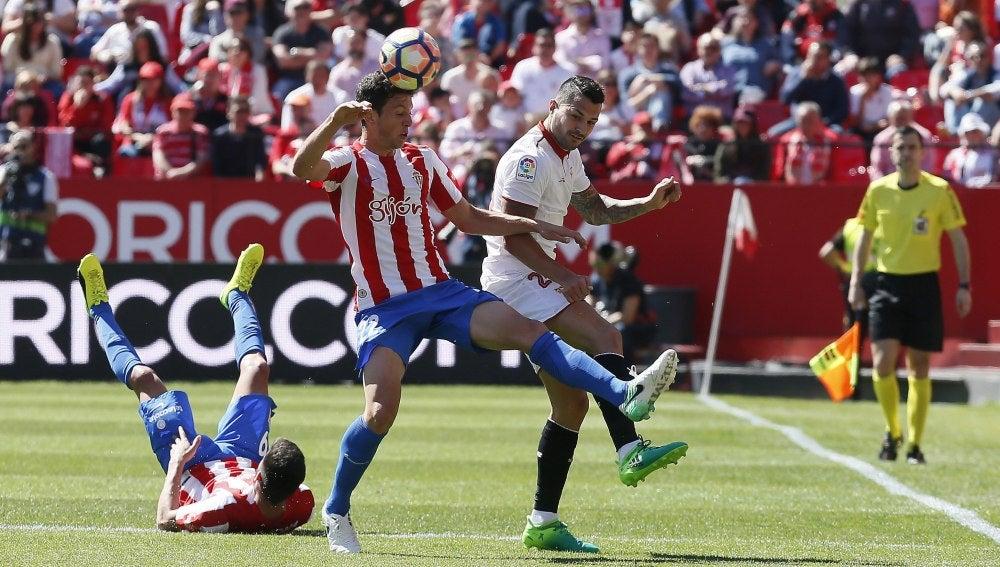Mikel Vesga y Vitolo disputan el balón en el Sporting - Sevilla
