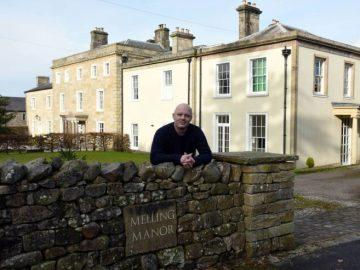 Dunstan junto a la casa que está rifando