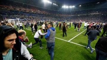 Los aficionados del Lyon huyen al terreno de juego