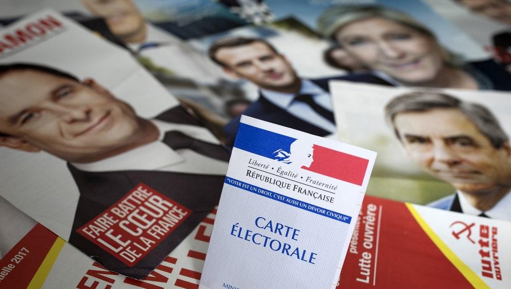 Una credencial para votar es fotografiada sobre los panfletos de los once candidatos