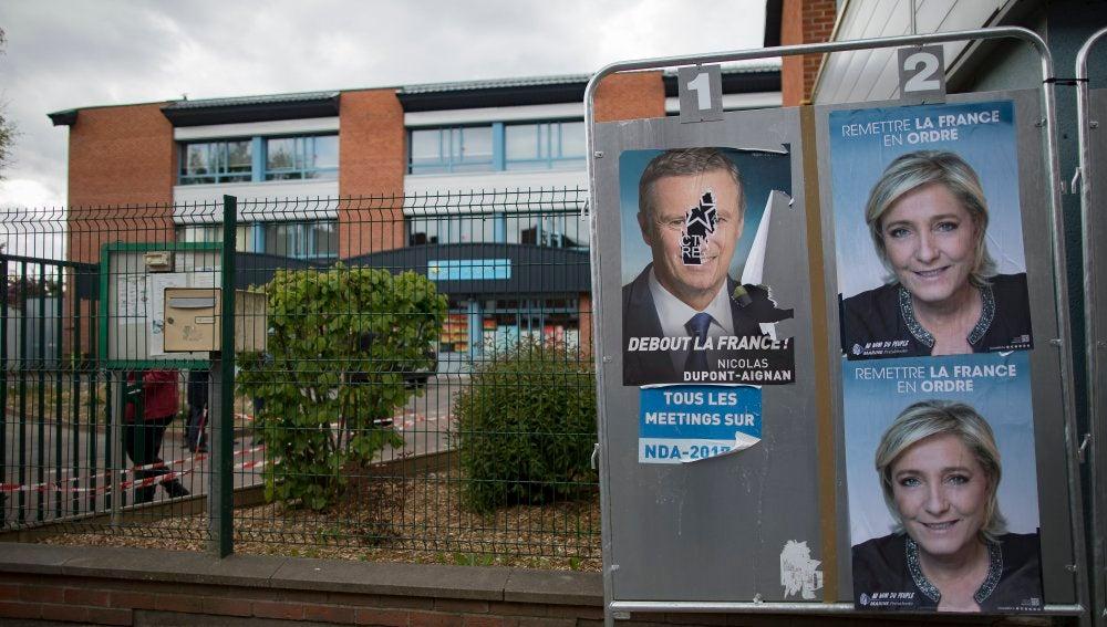 Carteles con alguno de los candidatos presidenciales en Francia adornan vallas publicitarias en el exterior de una mesa electoral en París (Francia)