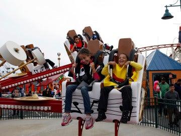 Dos niños montados en una atracción de feria