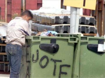 Un hombre buscando comida en un contenedor