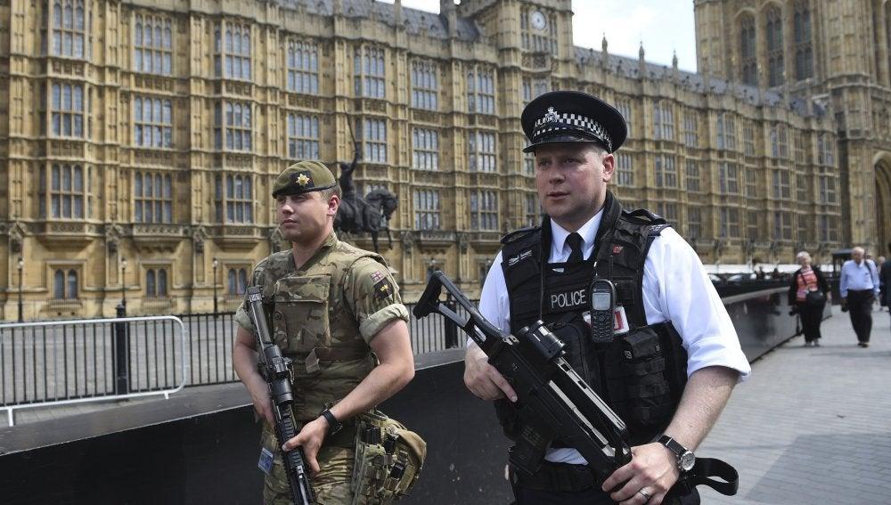 Un policía y un militar del Gobierno británico patrullando por la ciudad