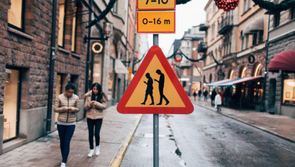 Señal de precaución por andar con los móviles