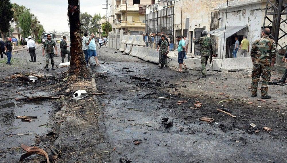 Varios policías y ciudadanos congregados en el lugar de una explosión