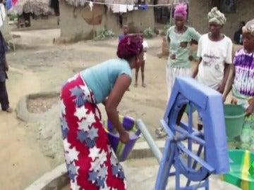 Mujeres africanas llenando agua de los pozos creados por  la asociación