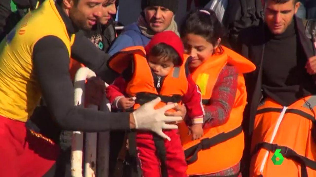 Un voluntario ayuda a un grupo de refugiados a llegar a tierra