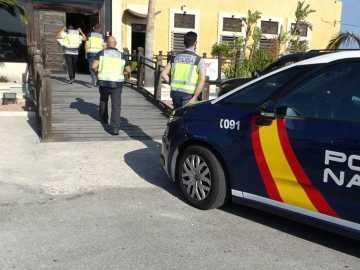 Agentes de la Policía Nacional de Elche accediendo al establecimiento en el que la víctima fue estafada.