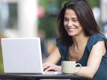 Una chica mira su portátil con una taza