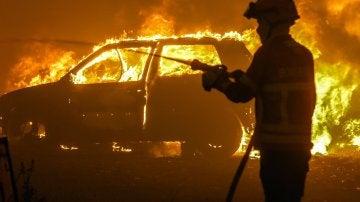 Un bombero intenta sofocar las llamas de uno de los coches atrapados en Portugal