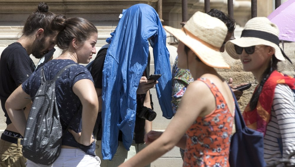 Un turista protegiéndose del sol con un chubasquero en la cabeza