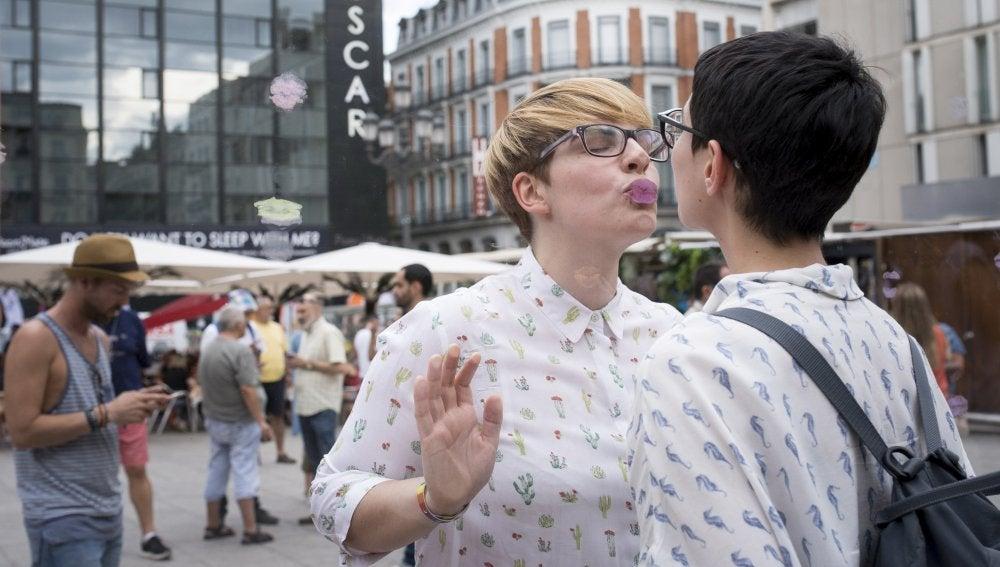 Una pareja se besa en el 'Muro de los besos perdidos' instalado en la plaza de Pedro Zerolo