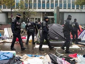 Agentes de policía galos inspeccionan las tiendas de campaña desalojo de un campamento en el distrito 19 de París, Francia