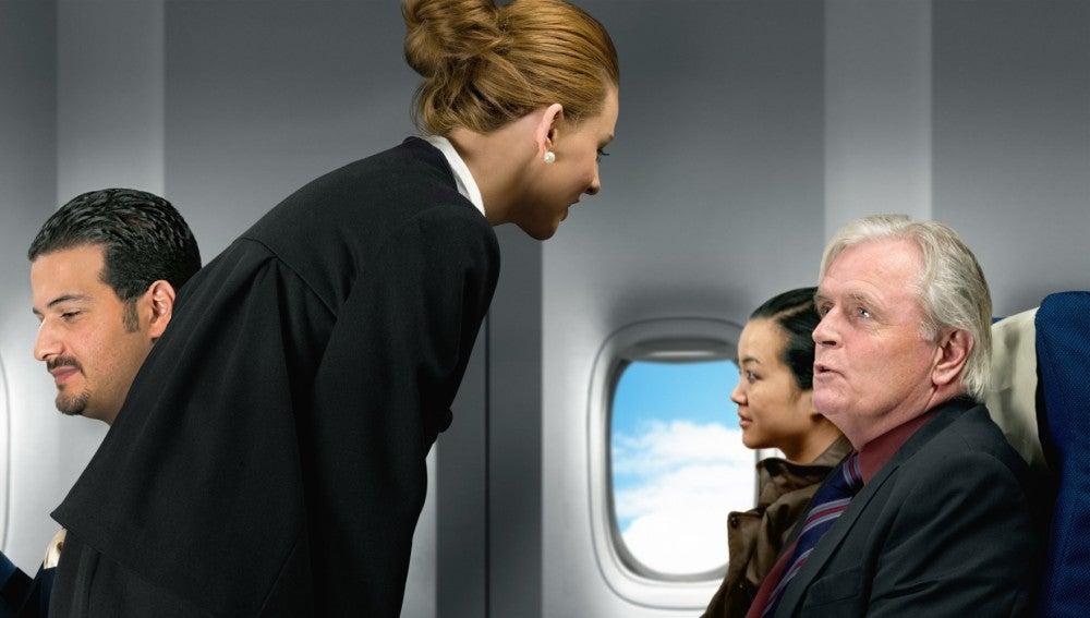Una azafata de vuelo atendiendo a un pasajero