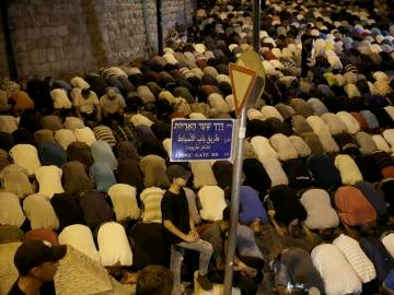 Ciudadanos palestinos rezan fuera de la Puerta de los Leones, la principal entrada a la mezquita de Al-Aqsa