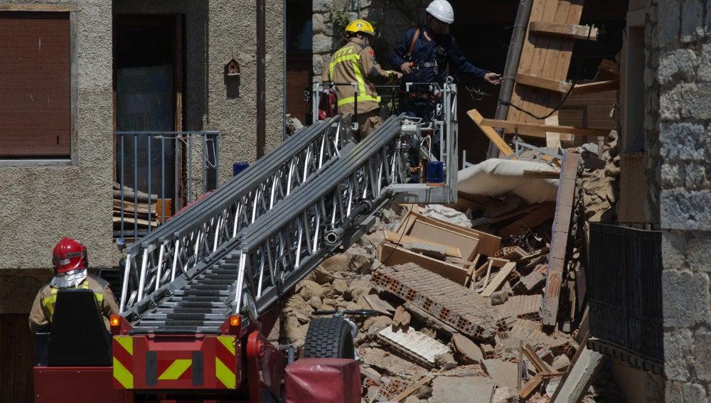 Miembros de los bomberos trabajando en las ruinas de una casa en Llanars (Girona) que se ha derrumbado provocando dos heridos