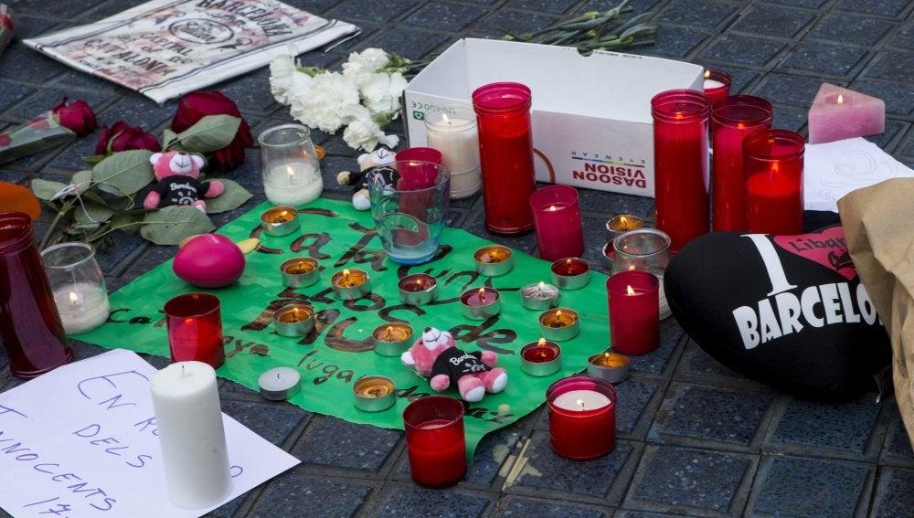 Varios transeúntes depositan mensajes y velas en el mosaico de Miró en las Ramblas