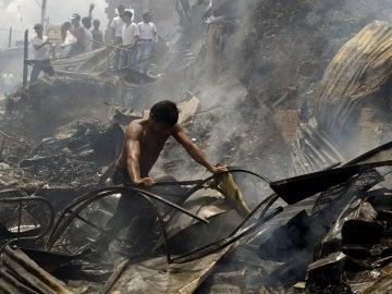 Un hombre busca sus pertenencias tras el incendio de Medellín