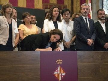 La alcaldesa de Barcelona, Ada Colau, acompañada de autoridades, firma en el libro de condolencias