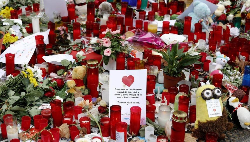 Mosaico de Miró cubierto por velas y flores
