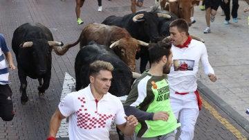 Unos mozos corren delante de un toro hoy durante el último encierro de San Sebastián de los Reyes