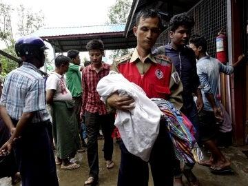 Un voluntario de la Cruz Roja lleva a un niño junto con mujeres desplazadas rohingyas del área de Maungdaw, ayer.