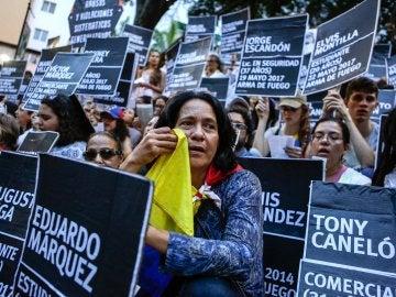 Manifestantes opositores participan en una protesta en memoria de las personas que perdieron la vida en medio de las protestas y de quienes permanecen arrestados