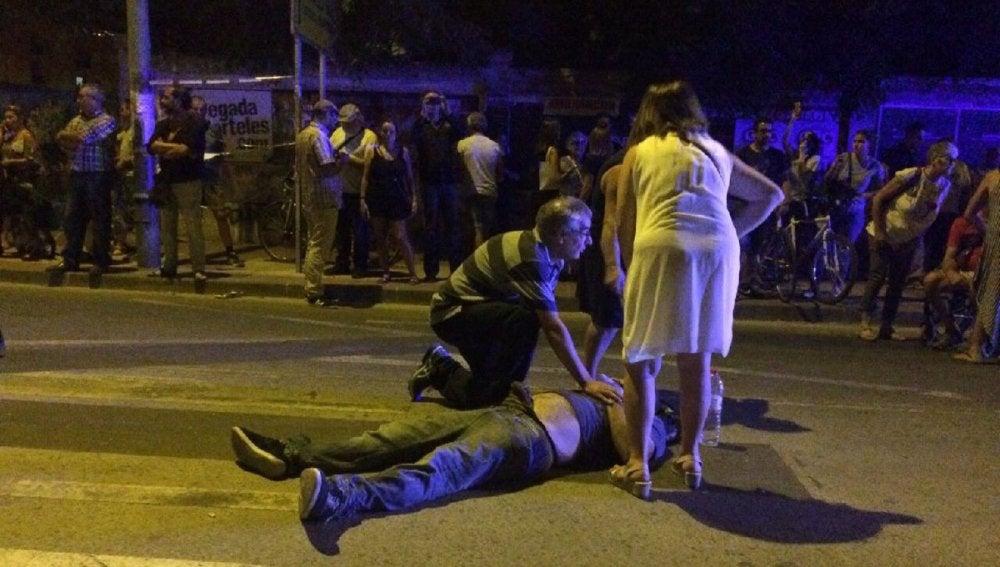 Un hombre atiende a uno de los manifestantes heridos