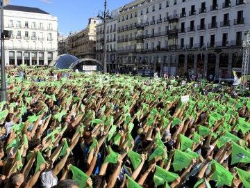 """Miles de personas convocadas por el Partido Animalista Pacma, en la Puerta del Sol de Madrid, portan pañuelos verdes para simular un """"chupinazo animalista"""" en una manifestación contra la tauromaquia"""