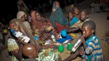 Una familia nigeriana come su ración de alimentos en un campamento de desplazados internos en Maiduguri (Nigeria)