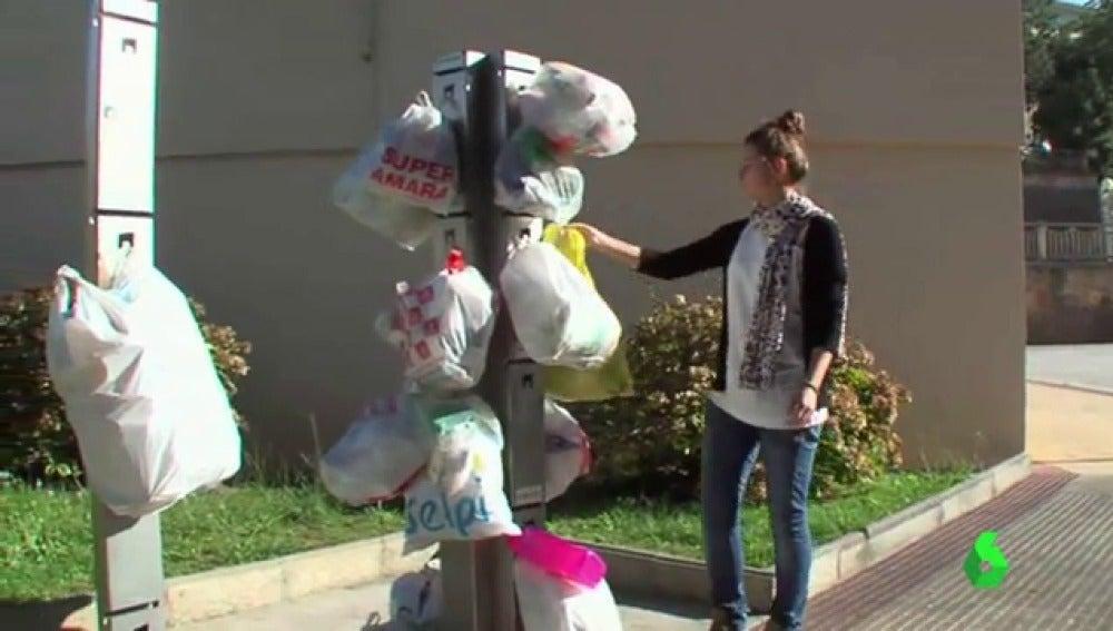 Una mujer coloca una bolsa de basura en una columna de reciclaje