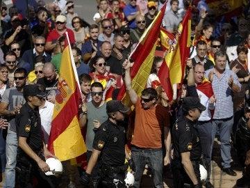 Un grupo de personas, con banderas españolas, aplaude a los agentes de la Policía Nacional en la entrada al pabellón Siglo XXI de Zaragoza