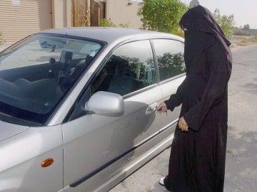 Una mujer saudí abre la puerta de un coche familiar en Riad, Arabia Saudi.