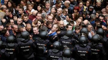 Agentes antidisturbios de la Policía Nacional forman un cordón de seguridad en los alrededores del colegio Ramón Llull de Barcelona