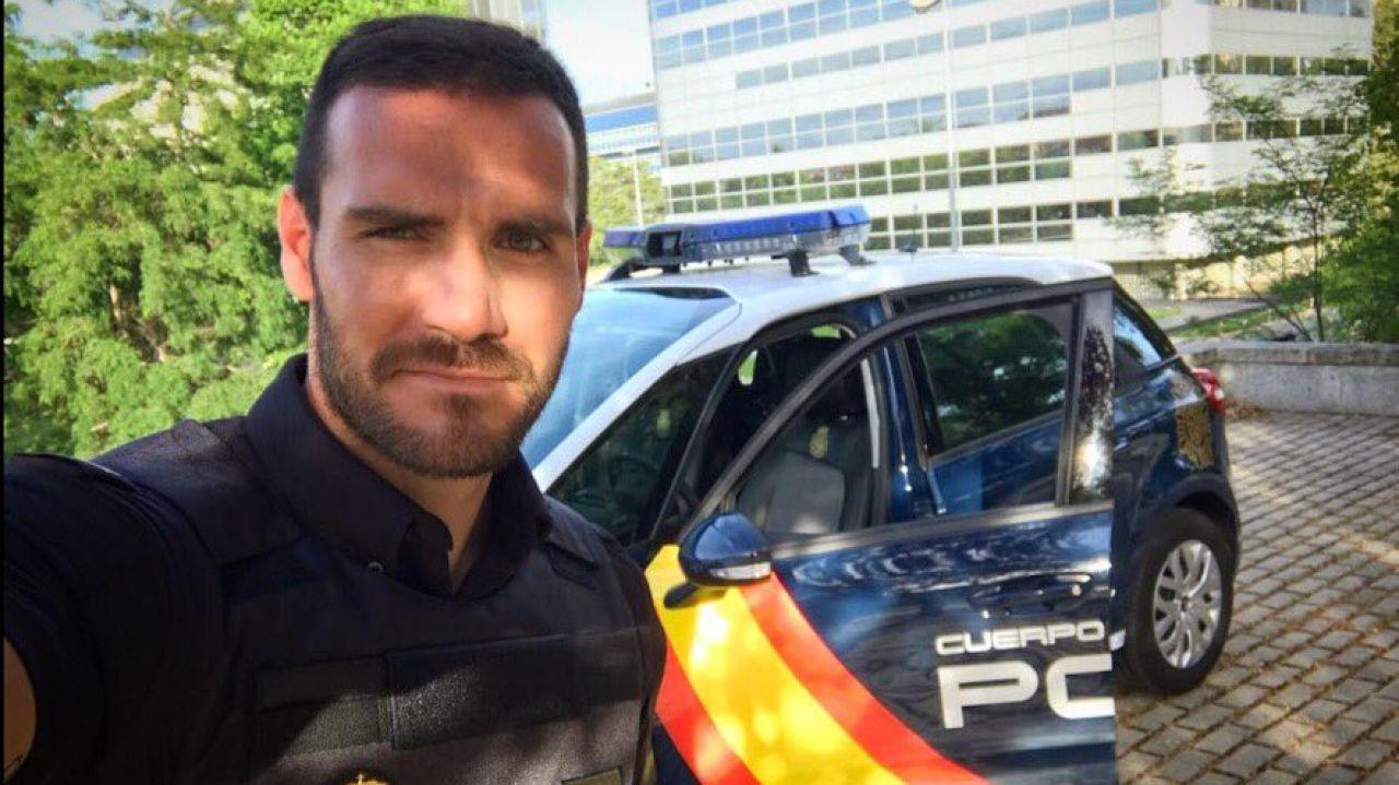Saúl Craviotto posa con su uniforme de Policía al lado de un coche patrulla