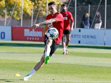 Torres patea un balón bajo la mirada de Diego Costa