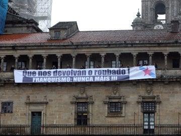 La portavoz del BNG en Bruselas, Ana Miranda, y el coordinador de Relaciones Internacionales, Rubén Cela, participan en un acto simbólico contra el expolio franquista en donde militantes colocaron un cartel en la fachada de la Catedral de Santiago