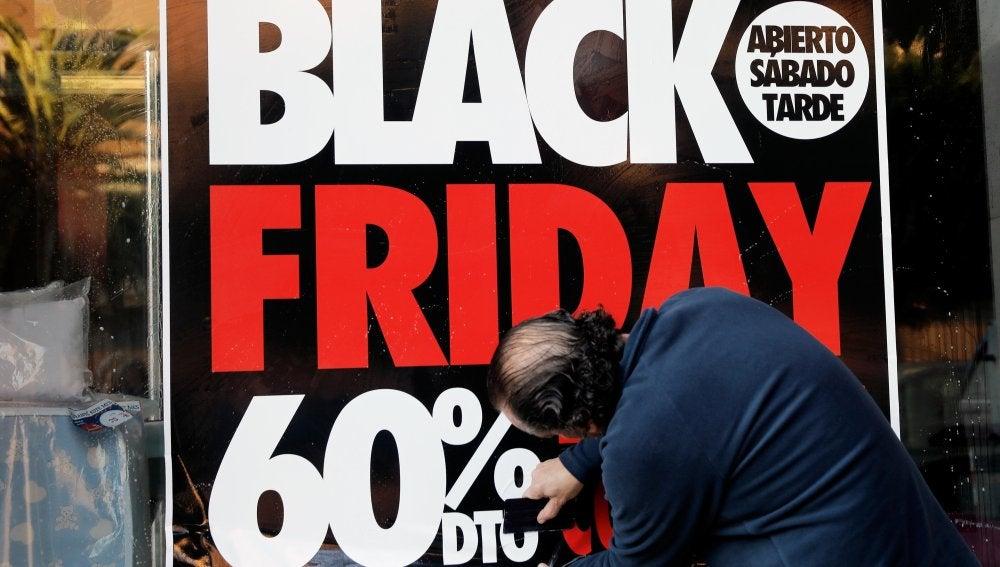 Un operario coloca un cartel en el escaprate de una tienda en la que anuncia grandes rebajas en el 'Black Friday'