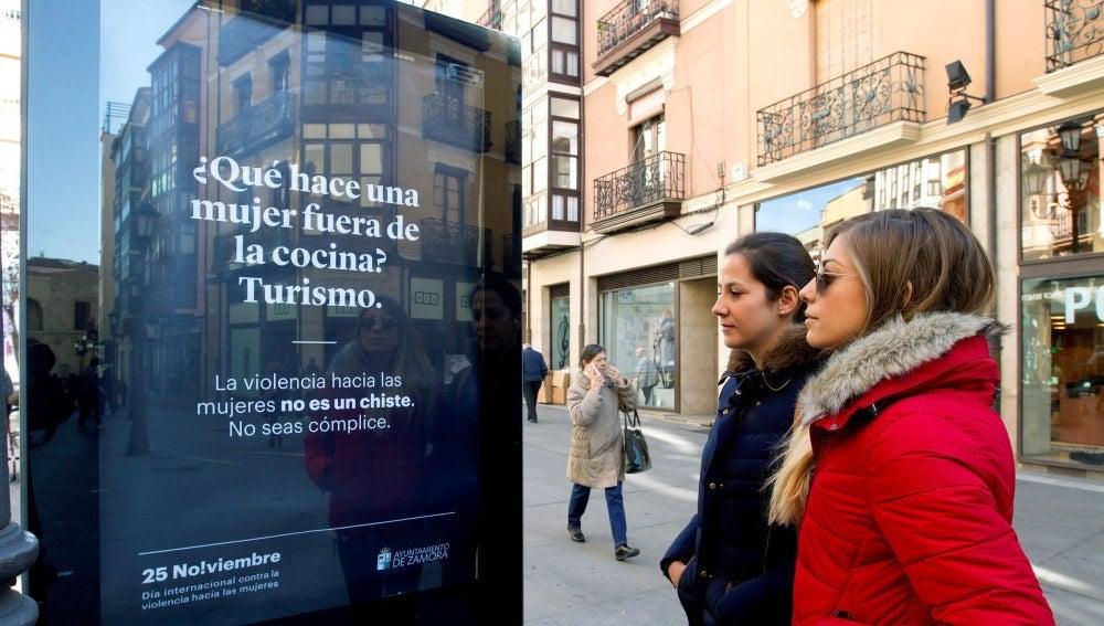 Dos mujeres observan uno de los carteles ubicados por las calles zamoranas de la campaña iniciada por el Ayuntamiento de Zamora