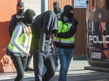 Agentes de la Policía Nacional acompañan a uno de los detenidos en Figueras, Gerona