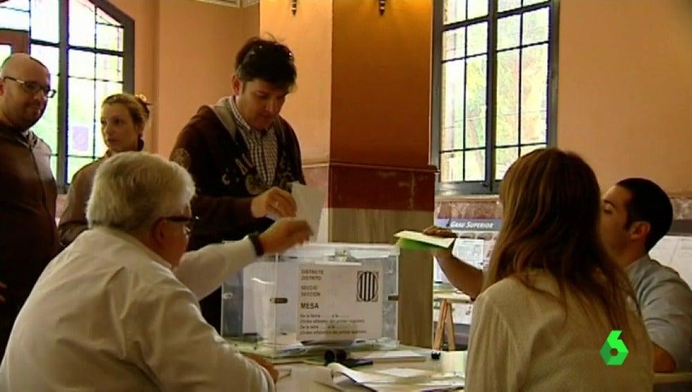 Unos ciudadanos depositan sus votos en una urna