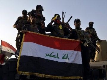 Imagen de archivo de soldados iraquíes sosteniendo la bandera nacional en el centro de Mosul