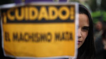 Una joven llevando un cartel contra el machismo