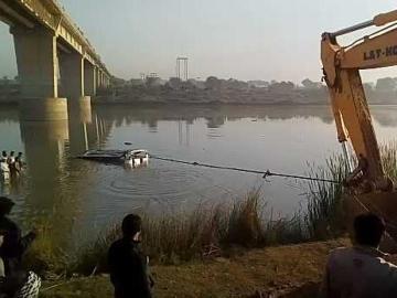 Trabajos para rescatar los restos del autobús accidentado en el río Banas