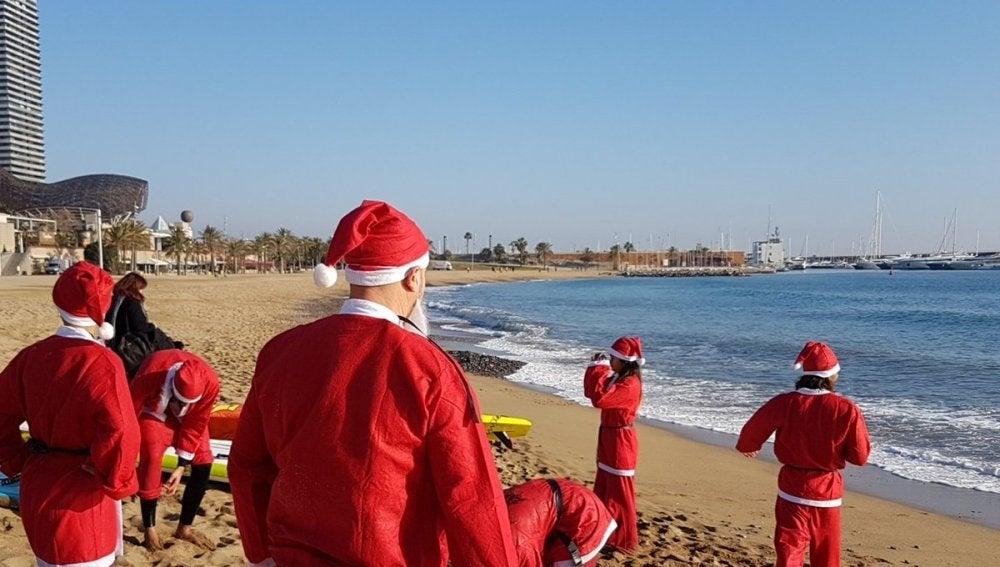 Personas disfrazadas de Papá Noel en tablas de pádel-surf